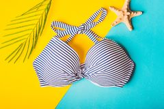 Взгляд сверху striped голубых и белых бюстгальтера и морских звёзд заплывания на голубой и желтой пастельной предпосылке скопируй Стоковое Изображение