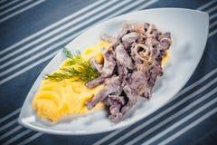 Взгляд сверху Stroganoff говядины с картофельными пюре на белой плите Плита на таблице с голубой скатертью в белизне стоковое изображение