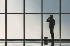 Взгляд силуэта молодого бизнесмена стоит в современном офисе с панорамными окнами Стоковые Фотографии RF