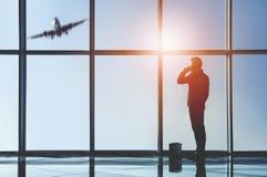 Взгляд силуэта молодого бизнесмена стоит в современном офисе с панорамными окнами Стоковые Фото