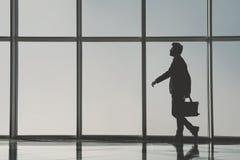 Взгляд силуэта молодого бизнесмена стоит в современном офисе с панорамными окнами Стоковое Фото