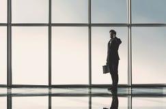 Взгляд силуэта молодого бизнесмена стоит в современном офисе с панорамными окнами Стоковое Изображение RF