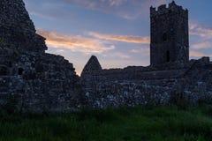 Взгляд силуэта руин аббатства Клары Augustinian снаружи Ennis монастыря как раз, графство Клара, Ирландия на заходе солнца стоковая фотография rf
