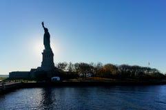 Взгляд силуэта статуи свободы около часа захода солнца стоковое изображение rf