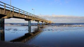 Взгляд сиротливого длинного моста на Балтийском море с песчаным пляжем в ветреном дне стоковая фотография rf