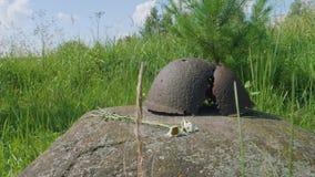Взгляд сломленного старого шлема на большом камне акции видеоматериалы