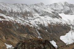 Взгляд снежной холмистой горы под темными облаками стоковые изображения