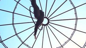Взгляд снизу на девушке которая поворачивает в кольцо для воздушной акробатики и делает шпагат акции видеоматериалы