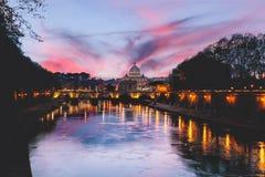 Взгляд собора St Peters в Риме на заходе солнца при света отражая на воде реки Тибра стоковая фотография