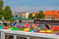 Взгляд соборов острова Tumski через touristic шлюпочную палуба с красочными стульями и подушками Стоковое Изображение RF