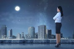Взгляд со стороны азиатской бизнес-леди стоя на террасе смотря ci Стоковые Фотографии RF