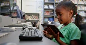 Взгляд со стороны Афро-американской школьницы используя цифровой планшет в библиотеке на школе 4k сток-видео