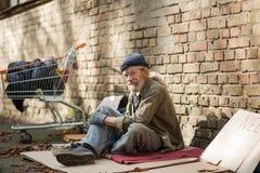 Взгляд со стороны бездомного человека сидя на картоне кирпичом стены Стоковая Фотография RF