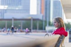 Взгляд со стороны белокурой женщины нося красную куртку сидя на benc стоковое изображение