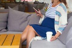 Взгляд со стороны беременной женщины используя цифровую таблетку на кафе Стоковое Фото