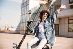 Взгляд со стороны беспечальной девушки в солнечных очках сидя на мотоцилк Стоковые Изображения