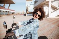 Взгляд со стороны беспечальной счастливой курчавой девушки в представлять солнечных очков Стоковое Изображение RF