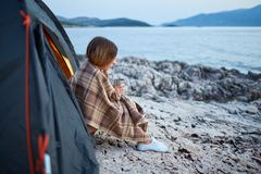 Взгляд со стороны девушки сидя около шатра, держа чашку душистого чая Стоковые Изображения
