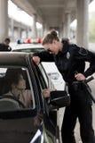 взгляд со стороны дубинки и говорить удерживания женщина-полицейского к сидеть молодой женщины стоковое фото