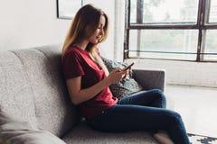 Взгляд со стороны женщины используя мобильный телефон пока сидящ на софе дома Стоковые Фото