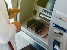 Взгляд со стороны женщины используя ATM держа бумажник отжимать PIN Стоковое Изображение