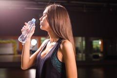 Взгляд со стороны красивой девушки в спорте одевает питьевую воду после разминки в спортзале Стоковое Фото