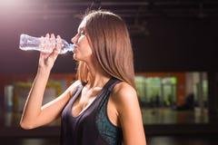 Взгляд со стороны красивой девушки в спорте одевает питьевую воду после разминки в спортзале Стоковые Фотографии RF