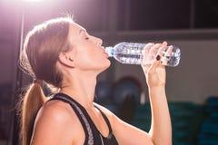 Взгляд со стороны красивой девушки в спорте одевает питьевую воду после разминки в спортзале Стоковые Изображения