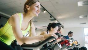 Взгляд со стороны красивой женщины усмехаясь пока задействующ на спортзале сток-видео