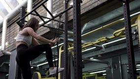 Взгляд со стороны - красивый тонкий молодой женский делать модели фитнеса Тяг-поднимает акции видеоматериалы
