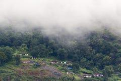 Взгляд со стороны леса деревни с небольшими домами стоковое фото