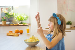 ВЗГЛЯД СО СТОРОНЫ: Маленькая девочка в голубом платье смешном ест спагетти от блюда Стоковые Фотографии RF