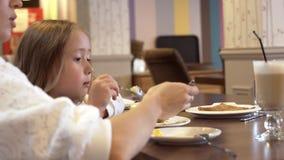 Взгляд со стороны - милая молодая мать и милая маленькая дочь едят совместно акции видеоматериалы