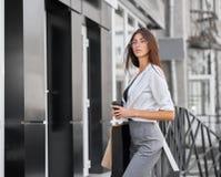 Взгляд со стороны милой модели представляя стоящий близко магазин, сумки нося и кофе стоковая фотография rf