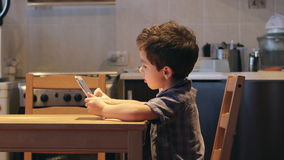 ВЗГЛЯД СО СТОРОНЫ: Милый маленький ребенок использует ПК таблетки на таблице дома Вскользь одежды сток-видео