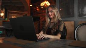 Взгляд со стороны Молодая бизнес-леди сидя на таблице и принимая примечания в тетради На таблице компьтер-книжка, smartphone и ча сток-видео