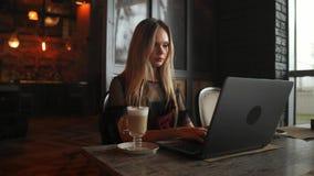 Взгляд со стороны Молодая бизнес-леди сидя на таблице и принимая примечания в тетради На таблице компьтер-книжка, smartphone и ча видеоматериал