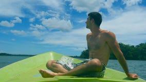 Взгляд со стороны молодого атлетического парня сидя на смычке шлюпки и смотря к красивому ландшафту природы на солнечный день Сча сток-видео