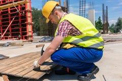 Взгляд со стороны молодого работника бить молотком ноготь молотком в древесину во время wo стоковая фотография