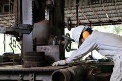 Взгляд со стороны молодого работника в форме и оборудовании для обеспечения безопасности режа кусок дерева на вертикальной машине Стоковое Фото