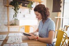 Взгляд со стороны молодой женщины используя планшет на кафе Стоковые Изображения