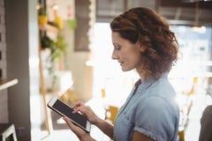 Взгляд со стороны молодой женщины используя цифровую таблетку Стоковое фото RF