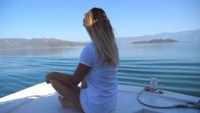 Взгляд со стороны молодой женщины сидя на смычке шлюпки и смотря к красивому ландшафту природы на солнечный день счастливая девуш сток-видео