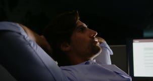 Взгляд со стороны молодой кавказской мужской исполнительной власти с руками за головой сидя на столе в современном офисе сток-видео