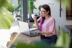 Взгляд со стороны молодой коммерсантки сидя на таблице в кофейне На чашке кофе и компьтер-книжке таблицы В белизне предпосылки Стоковая Фотография RF
