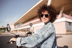 Взгляд со стороны молодой счастливой курчавой девушки в представлять солнечных очков Стоковая Фотография RF