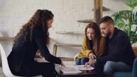 Взгляд со стороны молодые люди агента и покупателей недвижимости смотря план дома сидя на таблице в современном доме стиля просто сток-видео