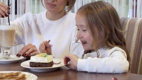 Взгляд со стороны - очаровывая девушка ест десерт сидя рядом с красивой молодой матерью видеоматериал