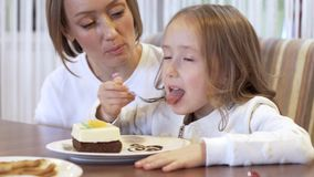 Взгляд со стороны - очаровывая девушка ест десерт сидя рядом с красивой молодой матерью сток-видео