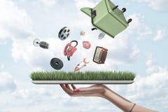 Взгляд со стороны планшета удерживания руки женщины с зеленой травой на экране и зеленом мусорном контейнере вверх ногами в возду стоковая фотография rf